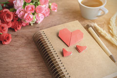 La tasse de café avec la fleur et le coeur rouge forment le papier et le bloc-notes Image stock