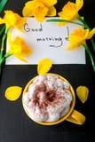 La tasse de café avec la jonquille jaune fleurit et cite bonjour sur la table noire Jour de mères ou jour des femmes Carte de voe Image libre de droits