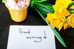 La tasse de café avec la jonquille jaune fleurit et cite bonjour sur la table rustique blanche Jour de mères ou jour des femmes C Images libres de droits