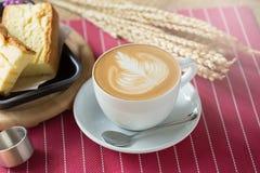 La tasse de café avec le bel art de Latte et le beurre durcissent, Selectiv Images stock