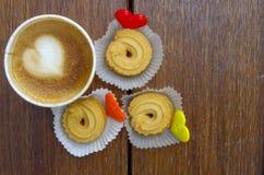 La tasse de café avec le biscuit et les boutons forment le coeur Images libres de droits