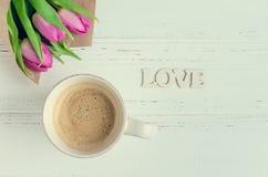 La tasse de café avec le bouquet des tulipes roses et le mot en bois AIMENT Photographie stock libre de droits