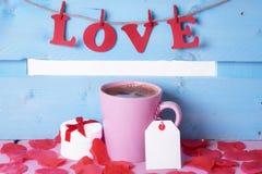 La tasse de café avec un cadeau et le mot aiment Photo libre de droits