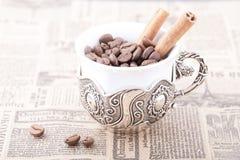 La tasse de café blanc a rempli de grains de café sur le journal avec de la cannelle Photographie stock libre de droits