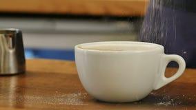 La tasse de café blanche et petite a servi avec l'art de latte du plat en bois banque de vidéos