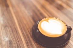 La tasse de café chaud de cappuccino avec l'art en forme de coeur de latte a fouetté la crème dans le ton de vintage, l'espace de Image stock