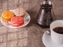 La tasse de café, d'une cafetière et de gâteaux s'est allumée par le soleil de la fenêtre Photos libres de droits