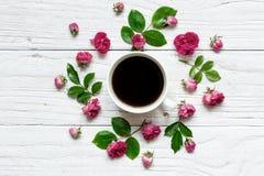 La tasse de café en fleur ronde de cadre avec des roses fleurit, des bourgeons, des pétales, des branches et des feuilles Photographie stock