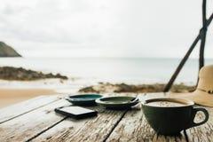 La tasse de café et deux soucoupes se tiennent sur une table en bois à côté du téléphone portable Images libres de droits