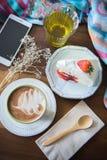 la tasse de café et la fraise délicieuse de gâteau et détendent le moblie o de temps Photographie stock libre de droits