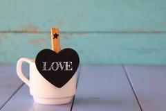 La tasse de café et peu de coeur forment le tableau avec le mot : AMOUR Photo stock