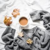 La tasse de café, grise chauffent le chandail tricoté surdimensionné, jaune sèchent toujours des feuilles sur le lit - la vie con photos libres de droits