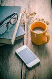 La tasse de café jaune placée sur une table en bois avec un téléphone intelligent, verres, livres, a séché des fleurs - modifiez  image stock