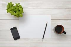 La tasse de café, l'usine d'intérieur, le livre blanc, le smartphone et le crayon sont sur une surface en bois Images stock