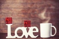 La tasse de café, le cadeau et le mot aiment Photos stock