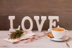 La tasse de café, les cadeaux, les fleurs et le mot aiment sur le fond en bois avec le copyspace Matin merveilleux le jour du ` s Images stock