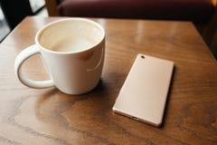 La tasse de café ont le baiser de rouge à lèvres sur la tasse et ont le téléphone intelligent pl Photos stock