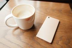 La tasse de café ont le baiser de rouge à lèvres sur la tasse et ont le téléphone intelligent pl Photo libre de droits