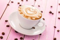 La tasse de cappuccino avec de la crème de coeur sur le fond en bois rose, boivent la photographie chaude de produit Photographie stock libre de droits