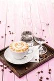 La tasse de cappuccino avec la mousse de coeur, ensemble de tasse de café avec des grains de café sur le fond en bois rose, boive photo libre de droits