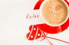 La tasse de cappuccino avec le coeur en bois et les notes détendent Images libres de droits