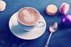 La tasse de cappuccino avec le macaron de gâteau, Noël joue Image stock