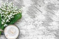 La tasse de cappuccino avec le muguet de ressort fleurit au-dessus de la table en bois blanche Photographie stock libre de droits