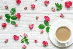 La tasse de cappuccino ou de café chaud avec du lait sur la soucoupe blanche avec la composition en fleurs faite en rose de rose  Photo libre de droits