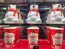 La tasse de culbuteur d'ours blanc et le seau de maïs éclaté ont placé le coke sur l'étagère au cinéma photo libre de droits