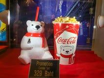 La tasse de culbuteur d'ours blanc et le seau de maïs éclaté ont placé le coke sur l'étagère au cinéma image stock