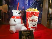 La tasse de culbuteur d'ours blanc et le seau de maïs éclaté ont placé le coke sur l'étagère au cinéma image libre de droits