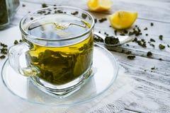 La tasse de dreen le thé avec le citron sur une table Photographie stock