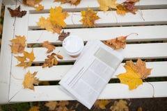 La tasse de journal et de café sur le banc en automne se garent Image stock