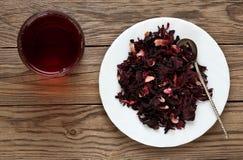 La tasse de ketmie de thé et de ketmie part sur un plat Photographie stock libre de droits