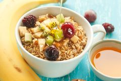 La tasse de l'avoine s'écaille avec la cerise, le kiwi, la mûre, l'oeuf, la noix et le miel dans la petite tasse sur une table en Photographie stock libre de droits