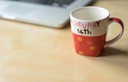 La tasse de la valentine vide avec le chemin de coupure et un ordinateur portable, l'espace de copie sur la table en bois Images stock