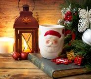 La tasse de Santa avec le fond de décoration de Noël Image libre de droits