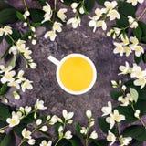 La tasse de thé avec le thé vert et le jasmin fleurit sur le fond en pierre Vue supérieure, configuration plate Photographie stock libre de droits