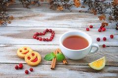 La tasse de thé avec les biscuits et le coeur de canneberge forment Photographie stock libre de droits