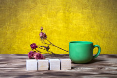 La tasse de thé, cubes en bois et sèchent les fleurs roses sur le nouveau verrat en bois photographie stock libre de droits