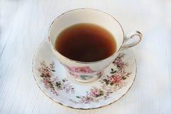 La tasse de thé dans une rose a modelé la tasse de thé et la soucoupe de porcelaine Image libre de droits