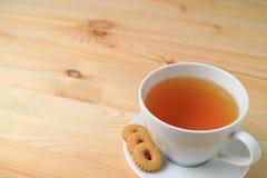 La tasse de thé et de biscuits chauds a servi sur le Tableau en bois naturel, avec l'espace libre pour la conception Photo libre de droits
