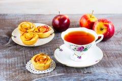La tasse de thé et les petites roses de pomme ont formé des tartes Photos stock