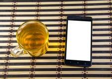 La tasse de thé et smartphone sur un tapis en bambou Photos stock