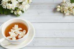 La tasse de thé, miel de versement d'une cuillère dans un pot, jasmin fleurit sur un fond en bois clair Copiez l'espace Photographie stock libre de droits