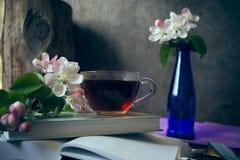 La tasse de thé sur le livre avec la fleur de pommier s'embranche Images stock