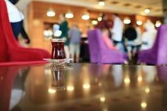 La tasse de thé turc sur une soucoupe est sur la table en verre image libre de droits