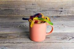 La tasse de vacances de Halloween avec la sucrerie worms sur la vieille table en bois photographie stock