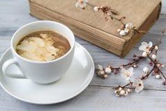 La tasse du café avec de la crème et du vieux livre avec la cerise de floraison s'embranche sur le fond en bois photographie stock