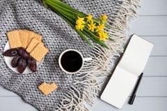 La tasse du café, du carnet à dessins, des casse-croûte et de la jonquille fleurit Vue supérieure, configuration plate Photographie stock libre de droits